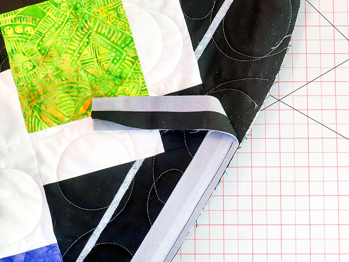 The binding strip is sewn with the narrower strip facing the quilt top