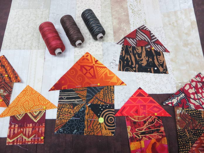 Three spools of thread on top of a quilt. Brother Innov-ís BQ3050 sewing and quilting machine, MuVit Digital Dual Feed Foot, SA195 MuVit Open-Toe Dual Feed Foot, Mary Ellen's Best Press, Banyan Batiks