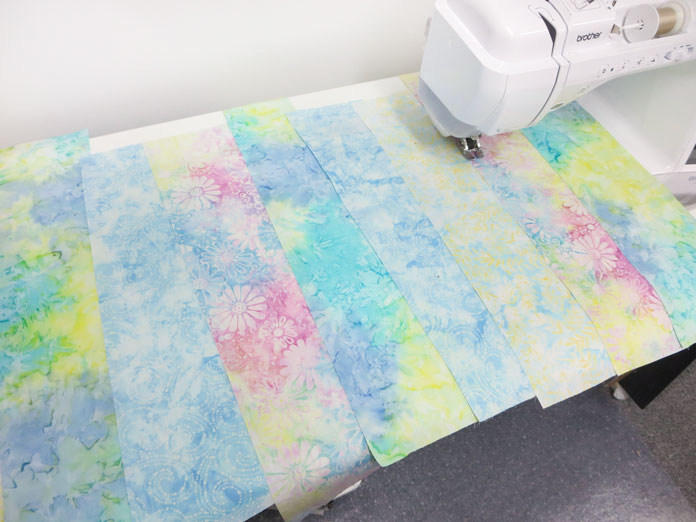 Fabric strips are topstitched by machine onto the backing fabric. Brother Innov-ís BQ3050 sewing and quilting machine, MuVit Digital Dual Feed Foot, Sugar Crystals collection by Banyan Batiks