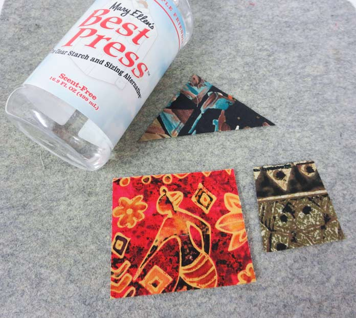 """Three pieces of fabric and a bottle of Mary Ellen's Best Press on a pressing mat. Brother Innov-ís BQ3050 sewing and quilting machine, Mary Ellen's Best Press, Brother SA185 ¼"""" Piecing Foot with Guide, Brother SA125 ¼"""" Quilting Foot, Olfa square ruler, MuVit digital dual feed foot"""