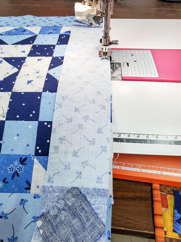Sewing a row of sashing to a row of blocks on the blue and white quilt top. Spectrum QAL2020 made with the Blue Stitch collection by Riley Blake Designs
