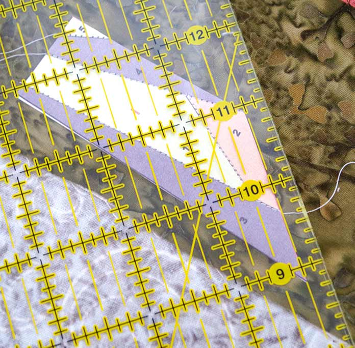 "The section of the bird can be seen through the yellow ruler grid. The ruler is placed along the edge that will be joined with the matching part of the bird. You can see that the edge of the ruler is straight at ¼"" ready to be cut with your rotary blade. You can see the paper through the ruler showing the different pieces that have been pieced together in gray and green fabric."