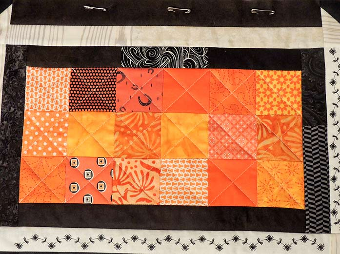 I completed the quilting in the center patch with a few more lines of quilting through the squares.