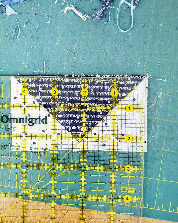 """Trimming the flying geese unit to 2½"""" x 4½"""" for Block 3 with Blue Stitch fabric collection by Riley Blake Designs."""