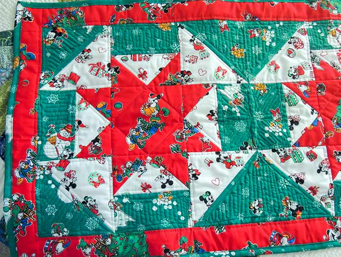 The quilting lines in the outside triangles are angled in to bring attention back to the center of the block; quilting the Vintage Holiday bed runner on the PFAFF performance icon
