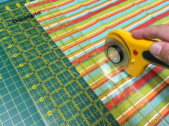 """Rotary cut the striped fabric 2½"""" wide with an Olfa rotary cutter, an Omnigrid ruler and a Unique cutting mat."""