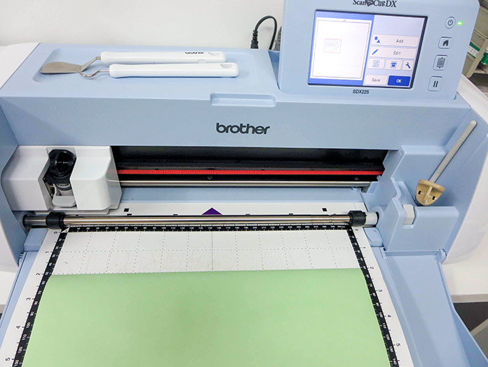 Place a Brother stencil sheet on the standard tack cutting mat, Brother ScanNCut SDX225, 505 temporary fabric adhesive spray, Brother stencil sheet, Brother standard tack cutting mat, Brother spatula and hook set