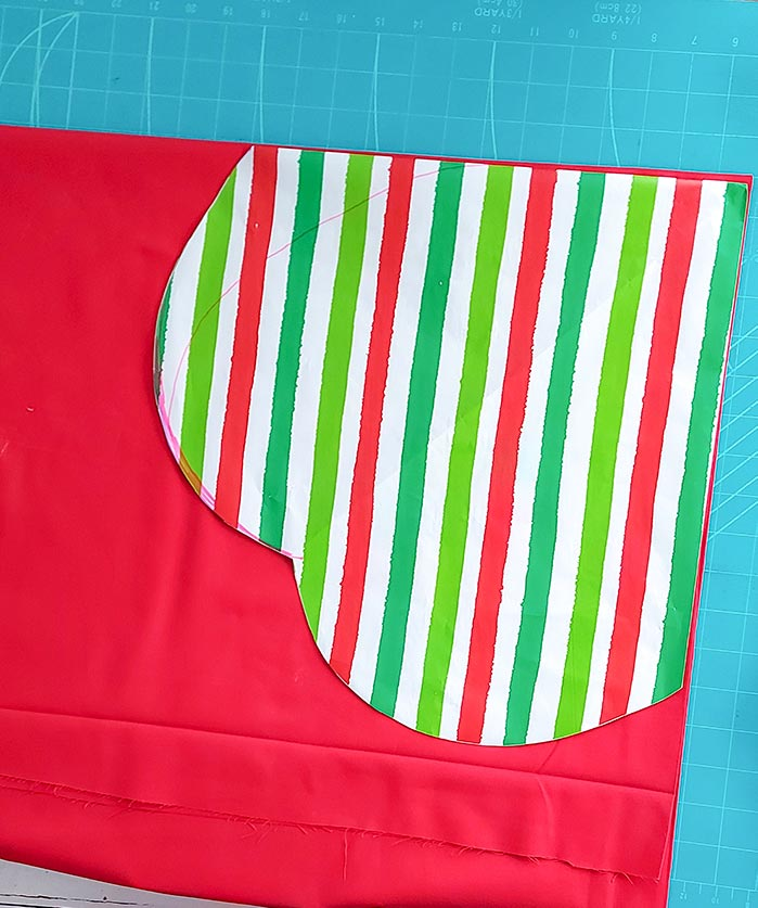 The template made of stripped wrapping paper is laid on the fold of the red fabric ready to cut the scalloped backing.