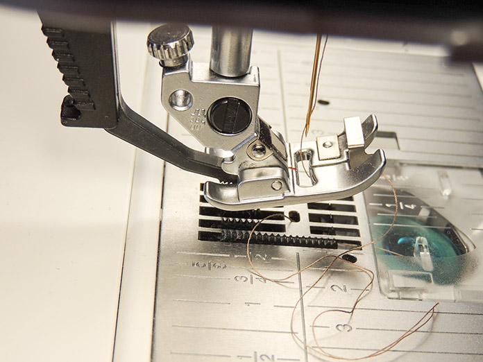 The IDT System attaches to the back of the presser foot and helps guide the layers of fabric evenly under the needle. PFAFF performance icon sewing machine, IDT system