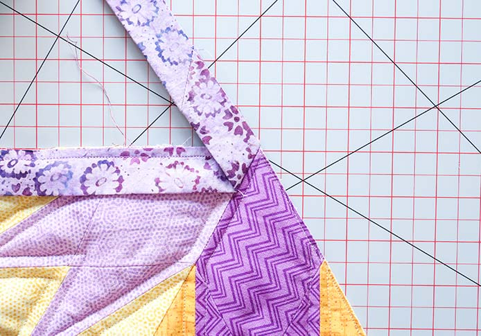 The sewn binding strip is folded away from the quilt so that its raw edge continues the line of the quilt's raw edge.