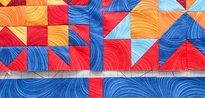 "A 1½"" x 1½"" square is sewn between two lattice fabric strips. Spectrum QAL 2020 made with Benartex Wave Texture collection, Fairfield Quilter's 80/20 Quilt Batting"