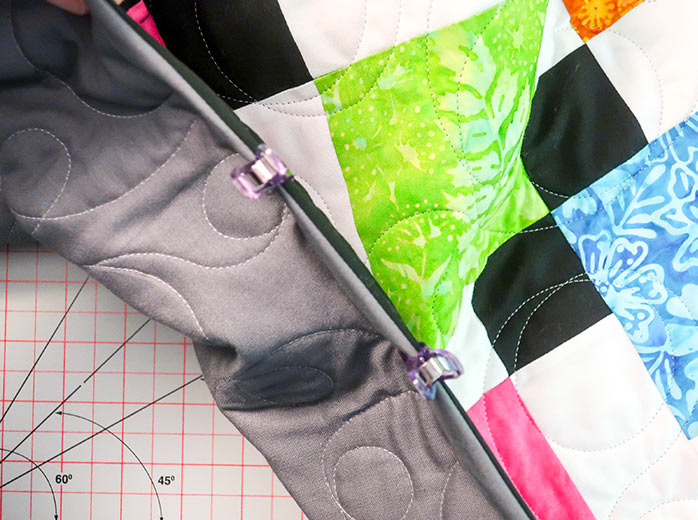 The binding is folded towards the back of the quilt and held in place with Clever Clips until it is ready to be sewn