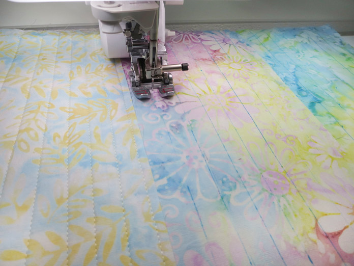 Quilting lines are stitched onto a table runner by machine with an open-toe presser foot. Brother Innov-ís BQ3050 sewing and quilting machine, MuVit Digital Dual Feed Foot, Sugar Crystals collection by Banyan Batiks