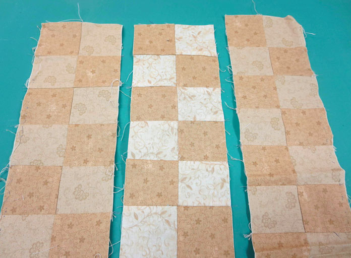 """Strips of pieced cream and beige fabric squares. Brother Innov-ís BQ3050 sewing and quilting machine, Mary Ellen's Best Press, Brother SA185 ¼"""" Piecing Foot with Guide, Brother SA125 ¼"""" Quilting Foot, Olfa square ruler, MuVit digital dual feed foot"""