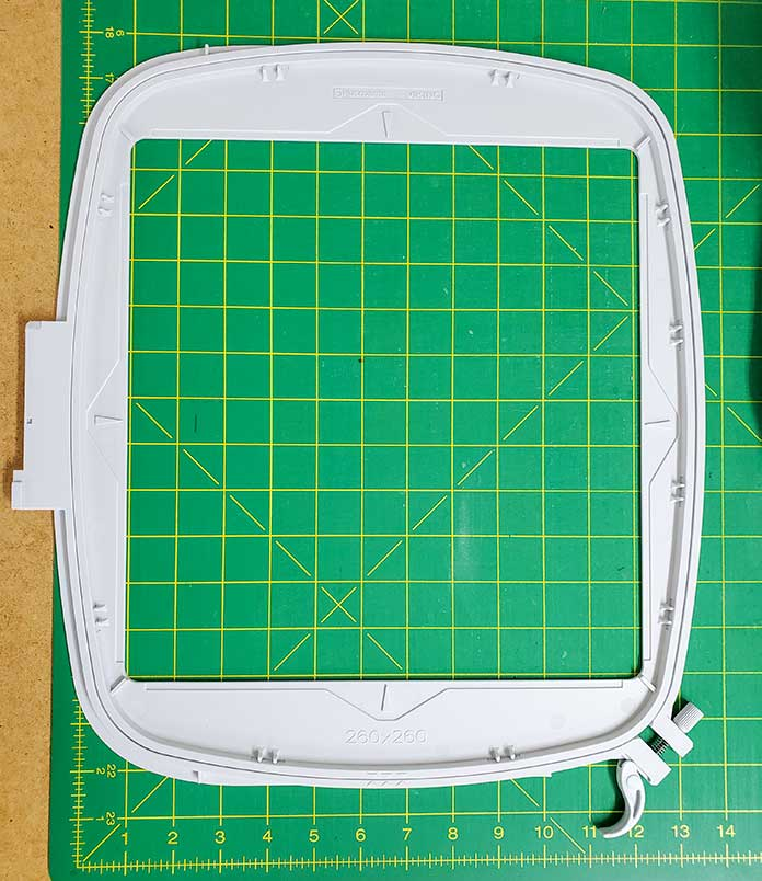 """The Husqvarna Viking Mega Quilters Hoop on a cutting mat. The inside of the 10"""" x 10"""" hoop is larger."""