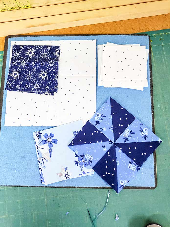 The pieces of a quilt block displayed on a design board; Spectrum QAL2020, Blue Stitch Fabric Collection