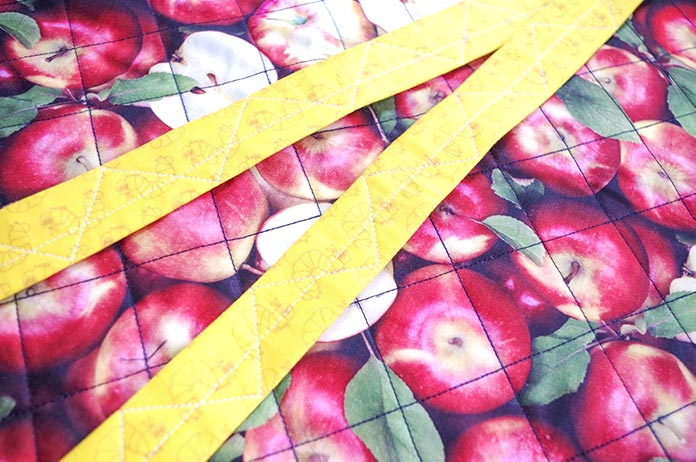 The yellow worm-patterned straps are lying on top of the apple fabric. The straps are quilted with zigzags and white thread from to bottom and the apple fabric is quilted with black thread in diagonals to great rhombus shapes.