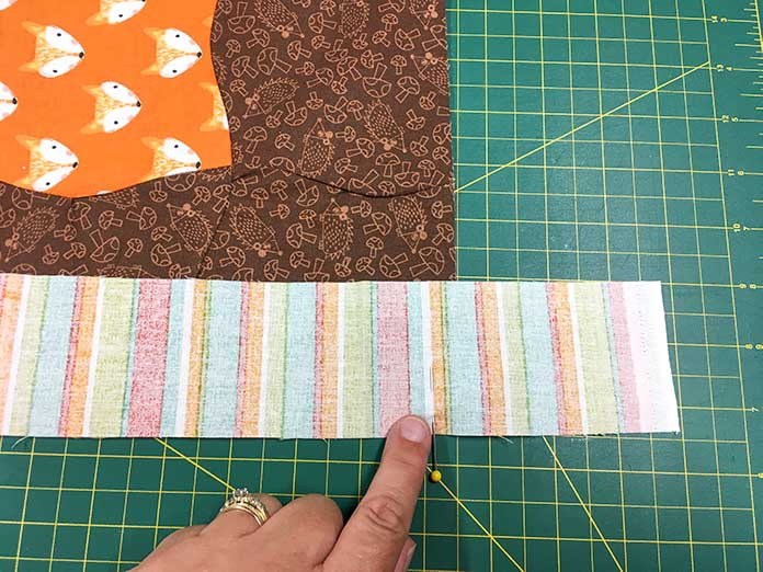 """Pin the two side borders to the sides of the quilt, making sure that you don't stretch the quilt or the border while you are pinning, and pin at both ends exactly ¼"""" from the end of the quilt."""