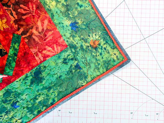 The flange binding is added to the quilt.