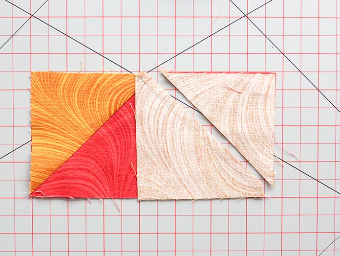 E and F fabric pieces are sewn together along both diagonal lines. A cut is then made halfway between the seams.
