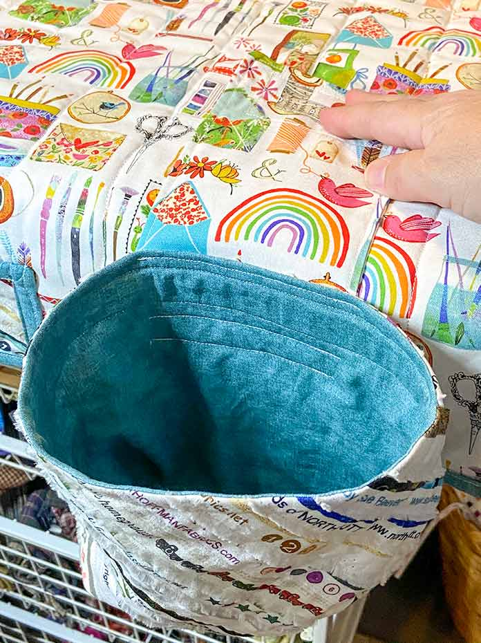 A hand holds the tab of the thread catcher bag in place on the sewing machine mat.