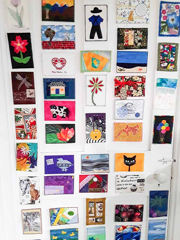 Fabric postcards displayed on the sewing room door, Brother BQ3050 sewing machine, Brother brayer, Brother spatula, Brother standard tack cutting mat