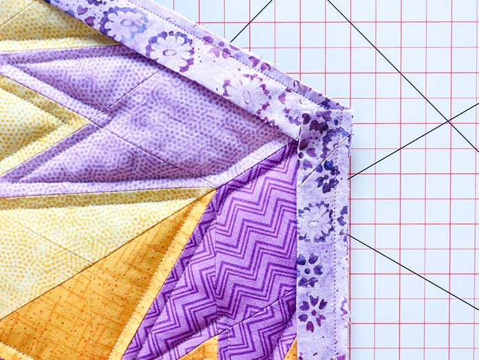 The binding strip is folded down and sewn along the quilt's next unbound edge.