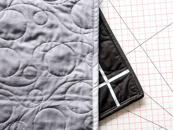 Showing the quilt's binding both back and front with two different fabrics used in the back