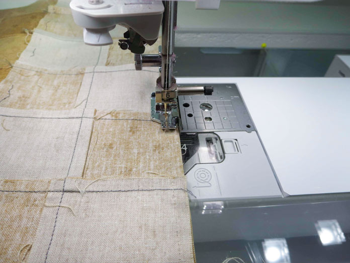 """Sewing strips of pieced squares together using the quarter inch foot with guide on a Brother sewing machine. Brother Innov-ís BQ3050 sewing and quilting machine, Mary Ellen's Best Press, Brother SA185 ¼"""" Piecing Foot with Guide, Brother SA125 ¼"""" Quilting Foot, Olfa square ruler, MuVit digital dual feed foot"""