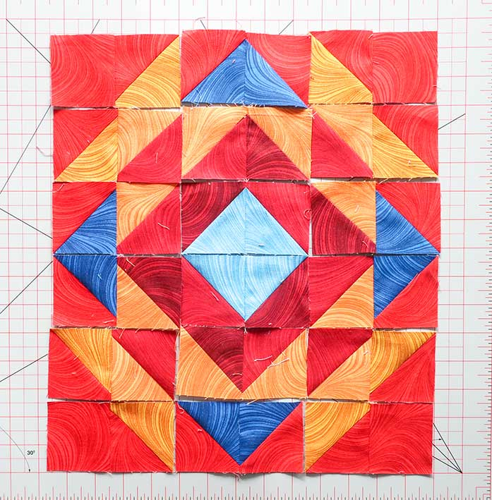 Place each sewn HST pair into their proper spot according to the layout diagram again before sewing them together into rows. Block 3 Spectrum QAL 2020 quilt design featuring fabrics from the Wave Texture collection by Benartex.