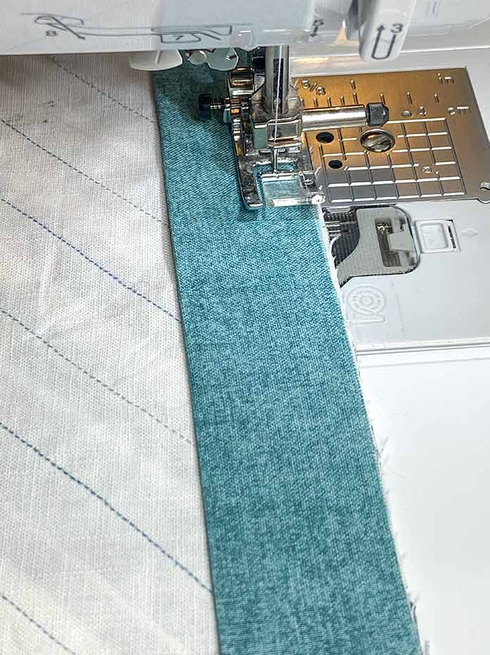 The binding is sewn to the back of the top edge and the right end of the pocket strip.