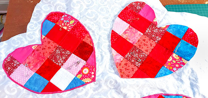 One red heart is shown with the pink applique stitches around it on the white background. One heart is shown pinned on ready to be appliqued.