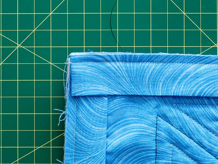 The strip is folded down and sewn along the quilt's edge. Gütermann threads