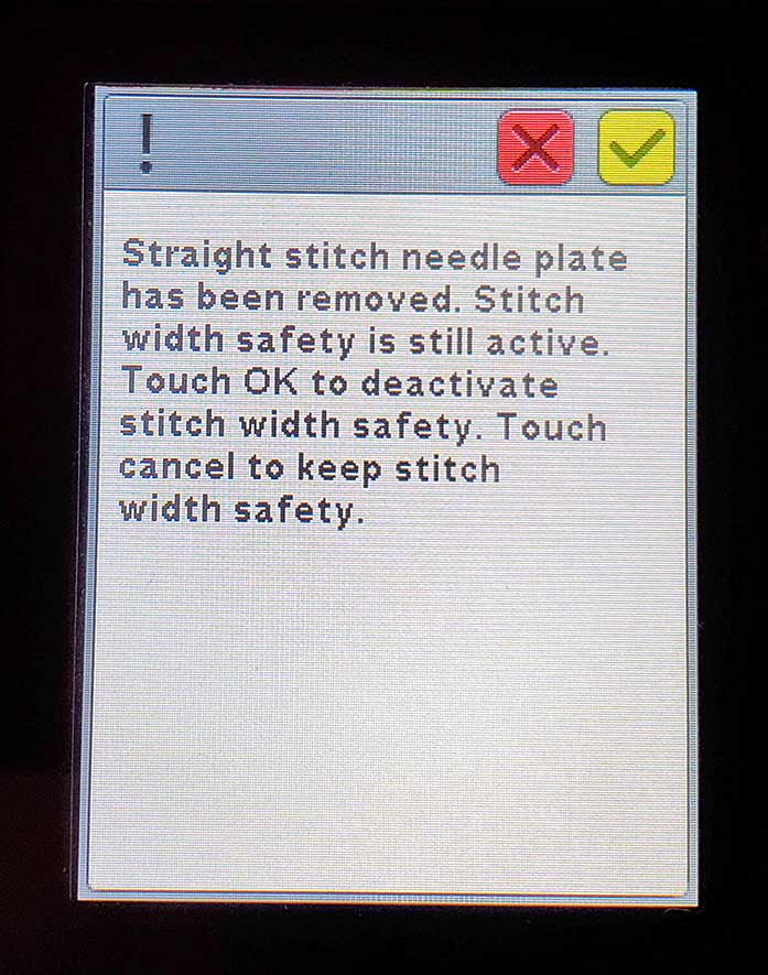 A pop-up message about stitch width safety on the Husqvarna Viking Brilliance 75Q sewing machine