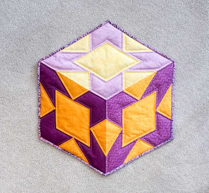 The binding on the hexagon quilt is complete after sewing down by hand or machine.