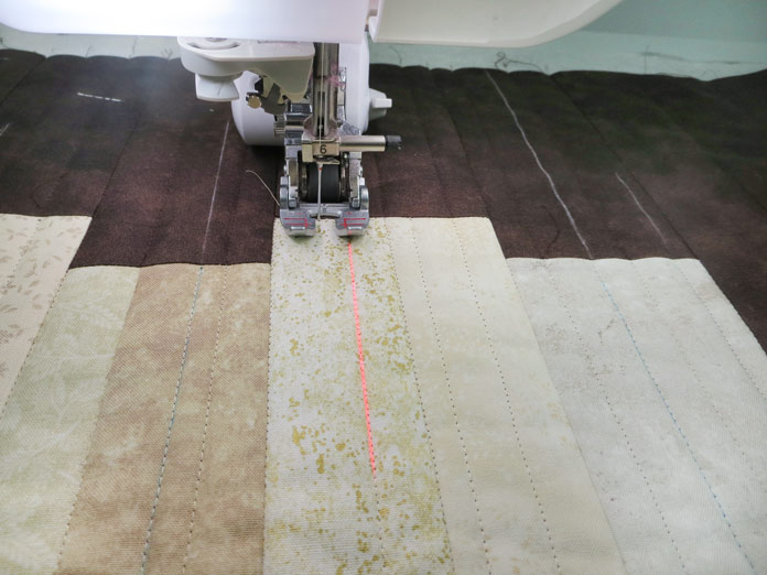 A laser vision guide shows on the fabric positioned under the presser foot of a sewing machine. Brother Innov-ís BQ3050 sewing and quilting machine, Brother SA186 Metal Open-Toe Foot, Brother SA204C Dual-Feed Stitch-in-the-Ditch Foot, Brother SA195 MuVit Open-Toe Dual-Feed Foot