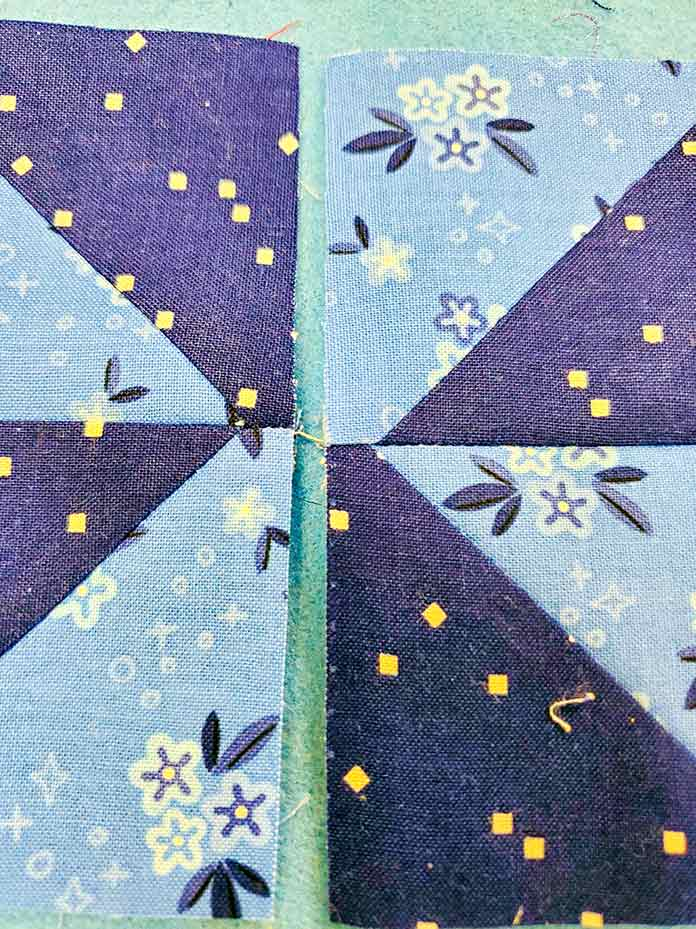 A line of stitching connects the two halves of the pinwheel block; Spectrum QAL2020, Blue Stitch Fabric Collection, Block 1