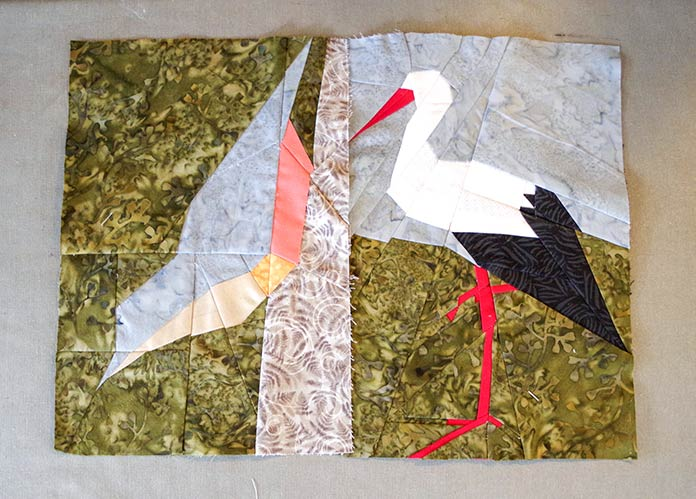 This picture shows the nuthatch which I completed first (greay, beign and orange body agains a green, leafy background, sitting on a brown patterned branch) on the left and the recently completed stork on the right. The stork is standing on the green, leafy background with its bent red legs and feet, the body is black and white with a long red beak, against the gray sky as a background. The grays and greens are the same for each bird and this ties them nicely together.