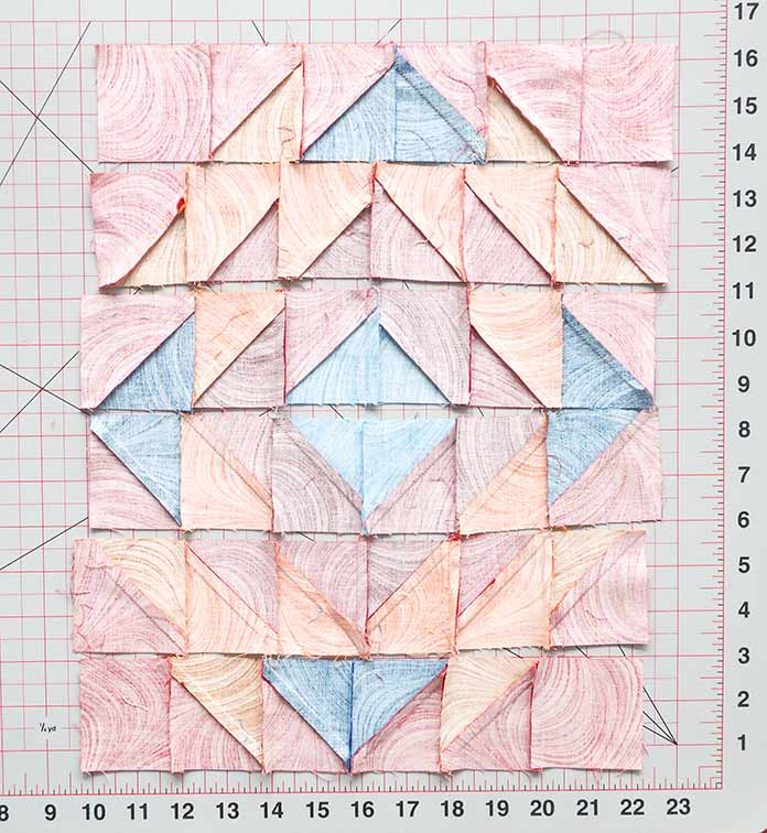 Lay out the block's rows according to the layout diagram. Ensure that each row's vertical seams are pressed in the opposite direction from the next row's vertical seams. Block 3 Spectrum QAL 2020 quilt design featuring fabrics from the Wave Texture collection by Benartex.