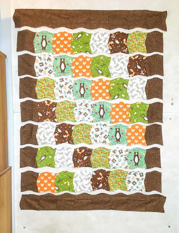The border blocks that have been cut with the marked Twisted Square Template are sewn together to the make the top and bottom borders and sewn to the ends of the rows of blocks that have already been sewn together.