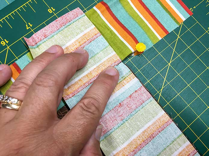 : The striped fabric border is pinned to the brown border with right sides together, and a pin is placed is exactly where the side seam is sewn.