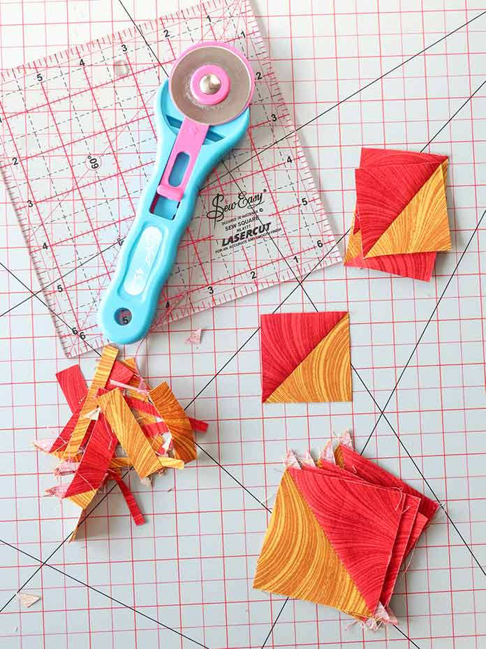 """Each HST set made from E and F fabrics is pressed and trimmed to measure 2""""x 2""""."""