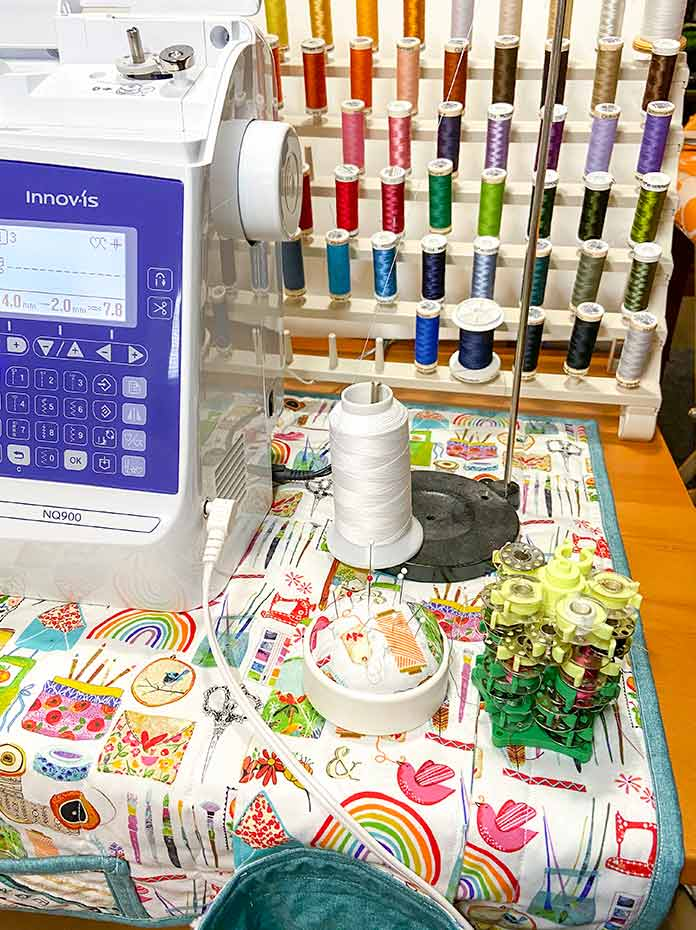 The CLOVER Create-a-Pincushion and CLOVER Stack 'N Store Bobbin Tower sitting on the right end of the sewing machine mat beside the sewing machine. A cone thread holder and the HEMLINE 60 Spool Thread Stand sit behind.