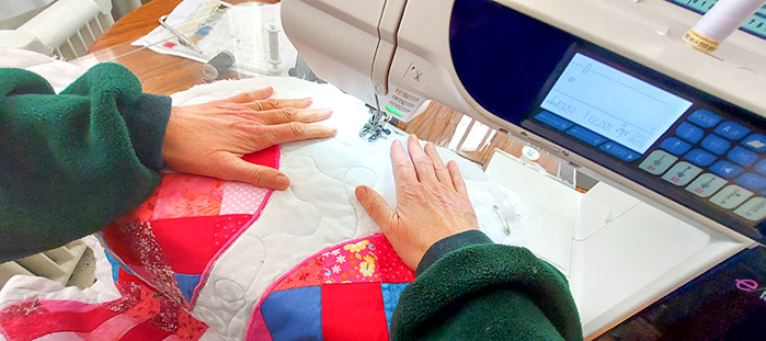 The appliqued hearts are seen on the white background. The sewing machine is in view with the patterns of the machine quilting on the white background visible between my hands.