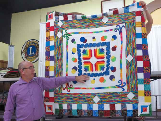Paul presenting one of his quilts during a trunk show.