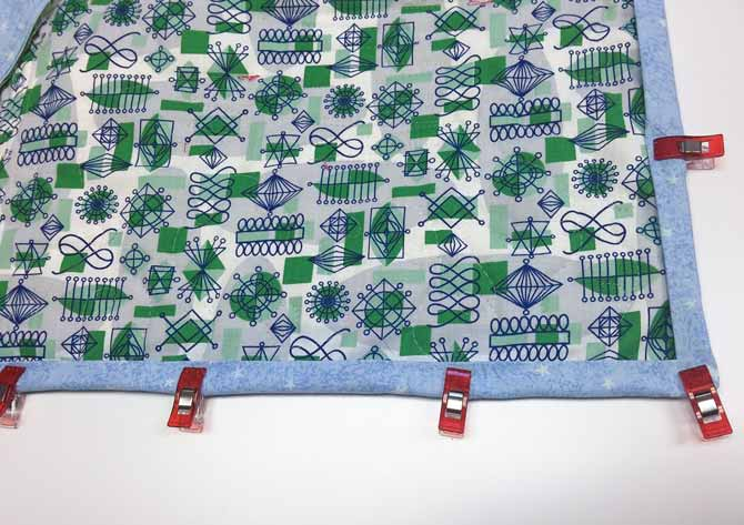 Back of quilt with binding held down by Clover Wonder Clips.