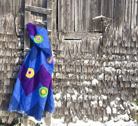 Flannel lap quilt hanging on ladder of barn.