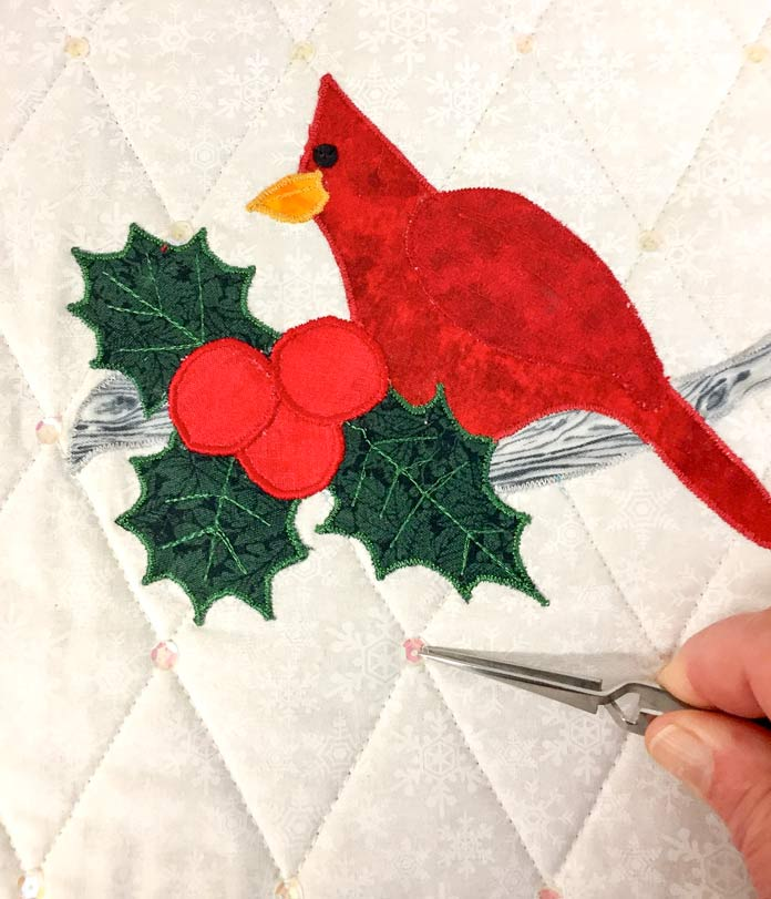 It's so easy to add sequins/embellishments to your quilts with the UNIQUE longarm reverse action tweezers! A look at my mini cardinal quilt for November via: quiltingintheloft.com