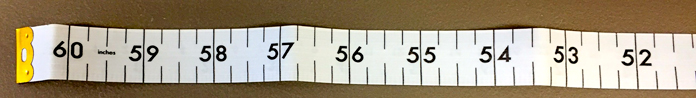 "Side two end of UNIQUE longarm zero center measuring tape, shows 60"" at both ends and zero in the center along with one inch and ¼"" increments."