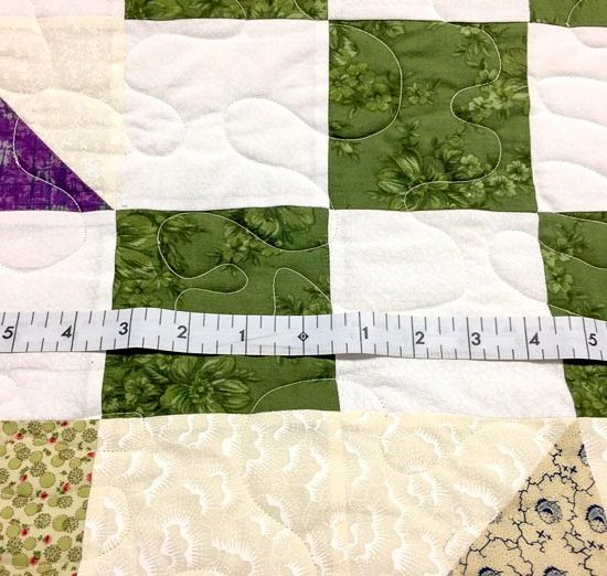 """UNIQUE longarm zero center tape measures 60"""" out from the center on both sides of the tape making it easy to measure a quilt width or length."""